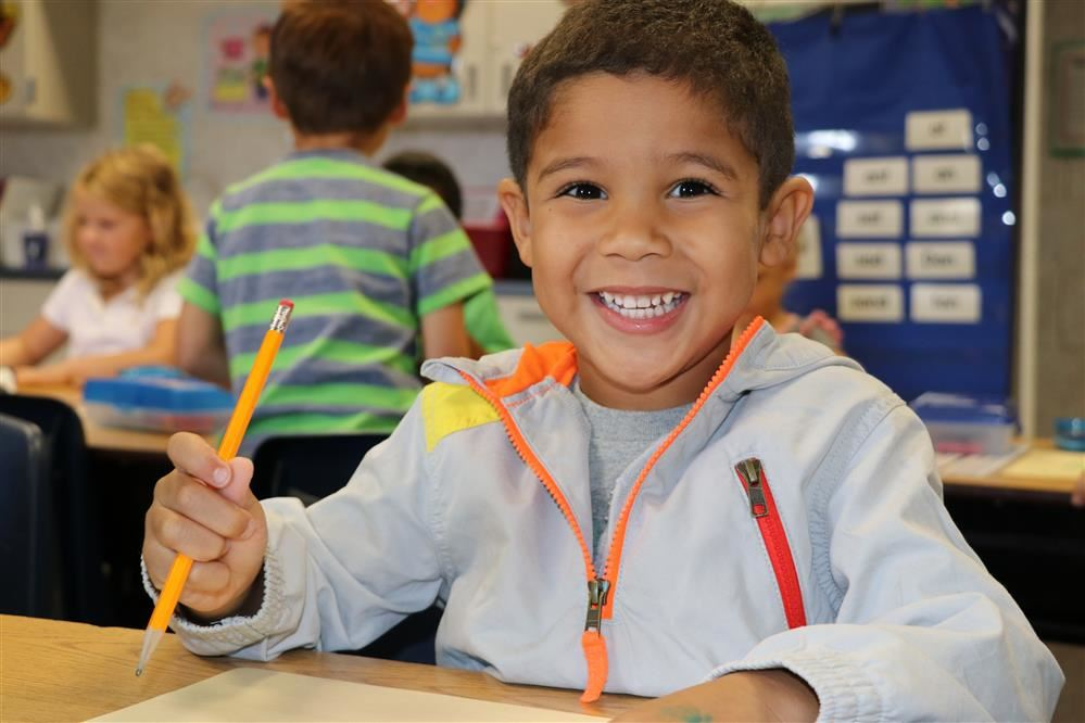 Picture of smiling child holding a pencil
